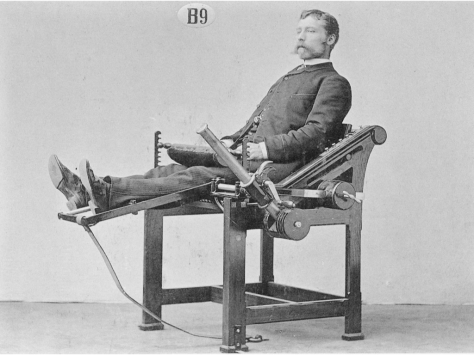 Moustachioed man at old fashioned exercise machine with a big lever