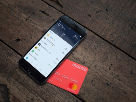 Monzo promotional image showing app on an iPhone and their distinctive coral coloured debit card